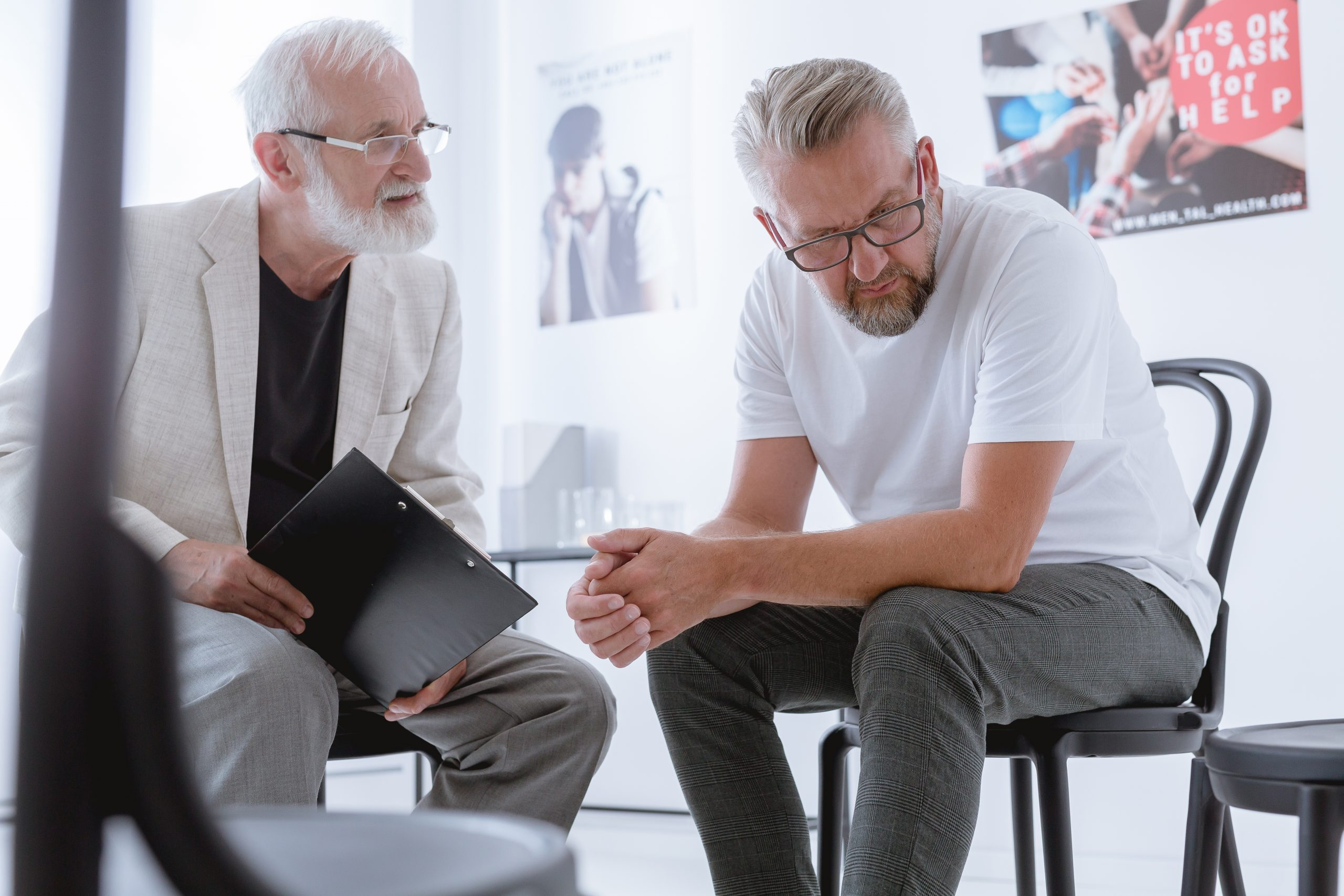 Older worried patient talking with his psychologist on a session